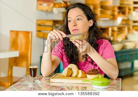Pretty brunette woman wearing pink shirt sitting by table inside bakery, applying butter to slice of bread, thoughtful facial expression.