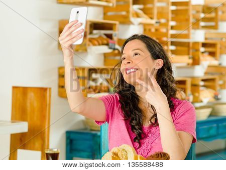 Pretty brunette woman wearing pink shirt sitting by table inside bakery, holding up mobile phone taking a selfie.