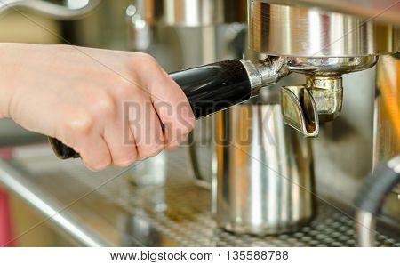 Closeup shiny metal coffee machine, hand inserting filter holder handle.