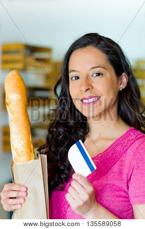 Pretty brunette wearing pink shirt holding up brown paper bag with bagutte inside, credit card in other hand smiling.