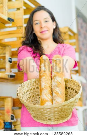 Pretty brunette wearing pink shirt holding up basket of baguettes smiling to camera, bakery customer concept.