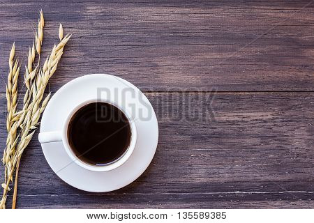 Cup of coffee and ears of oat on dark wooden table background. top view with copy space