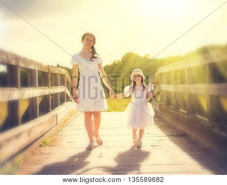 Mother and daughter walking on the sunny nature.