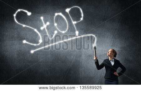 Young elegant businesswoman with flashlight draw word stop