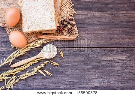 Ears of wheat and egg with slice of bread on a wooden table background. top view with copy space