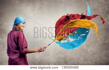 Young pretty artist woman with paint brush in hand