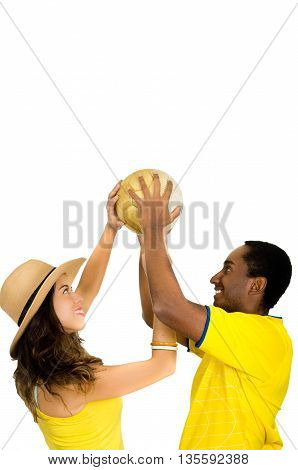 Charming interracial couple wearing yellow football shirts holding ball up in air between each other, profile angle white studio background.