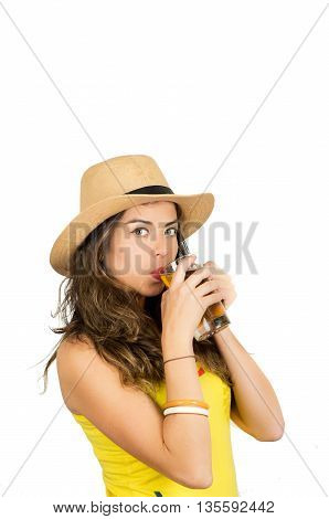 Hispanic brunette wearing yellow football shirt and hat, posing for camera while drinking from beer glass, white studio background.