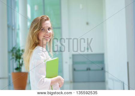 young happy female in white shirt with notepad