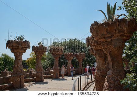 BARCELONA SPAIN - JULY 12 2013: Masterpieces of Antoni Gaudi in Guell park attract many tourists