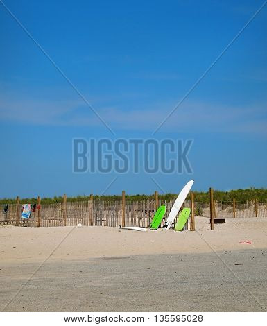 A surf board and two green bodyboards propped against a fence in the dunes at beach with grasses and a deep blue sky and sand.