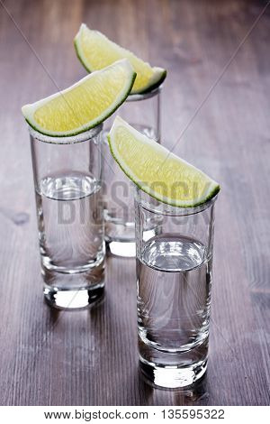 Three shots of tequila on a wooden table