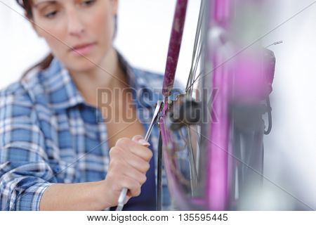 a woman is screwing tightly the fork at her bike