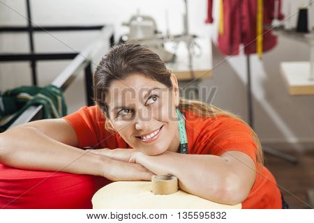 Smiling Female Tailor Leaning On Textile Spools