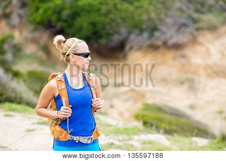 Woman hiking on trail with backpack in mountains. Recreation and healthy lifestyle outdoors in summer mountains. Trekking and activity concept in beautiful inspirational landscape.