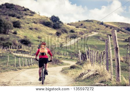 Mountain biker riding on bike in summer mountains landscape. Man cycling MTB on rural country road. Sport fitness motivation in inspirational fall landscape.