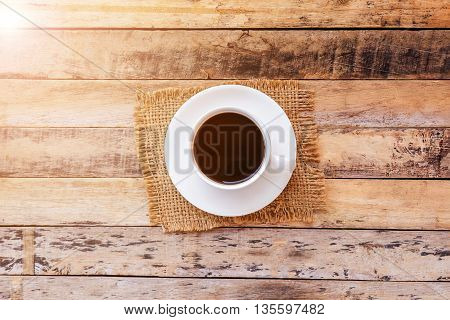 Cup of coffee on old wooden table background top view with copy space