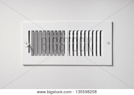 A heating/cooling vent register on the wall of a home with open/close lever
