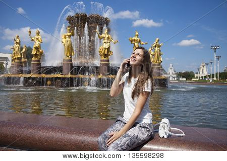 Beautiful young business woman calling by phone on the summer street