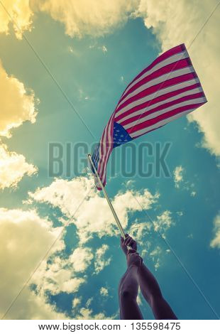 American flag with stars and stripes hold with hands against blue sky ( Filtered image processed vintage effect. )