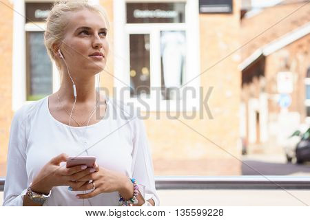 Beautiful young woman with blonde hair messaging on the smart-phone at the city street
