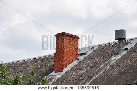 the roof of the old house with brick chimney