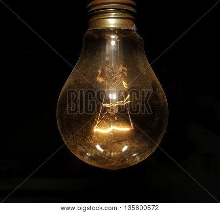 old electric light bulb glowing in dark
