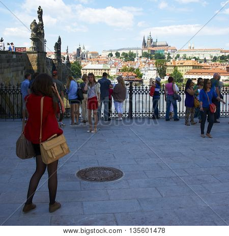 PRAGUE, CZECH REPUBLIC - SUMMER 2014 : Pedestrians and vendors (tourists) walking on the Charles Bridge, Vltava river, Prague the capital city of Czech Republic