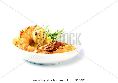 festive appetizer freshly roasted black tiger shrimps with garlic cream and dill garnish in a small serving bowl isolated with shadow on a white background close up with selected focus