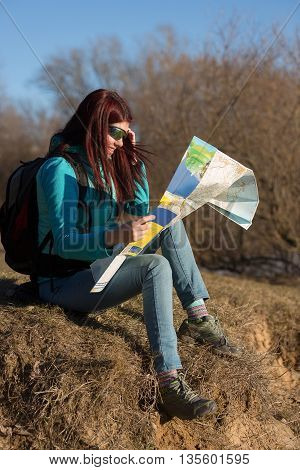 Young woman with backpack and map sitting on grass