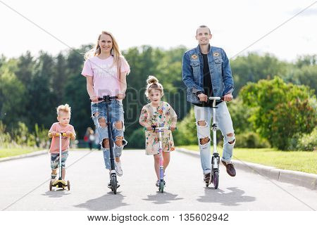 Family and children with scooters in the park