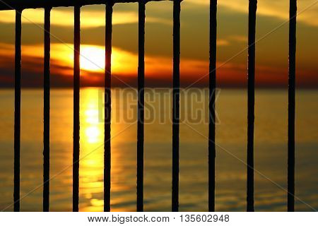 The sunset in the evening at the Baltic sea behind the bars