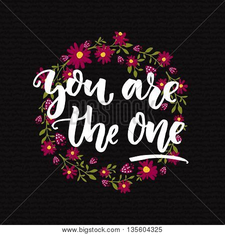You are the one. Inspirational quote calligraphy at dark background and floral wreath. Motivational saying for cards and posters