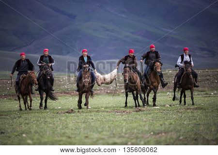 ISSYK KUL, KYRGYZSTAN - MAY 28, 2016: Nomad horse riders hold the goat carcass during traditional horse games in Issyk Kul, Kyrgyzstan.