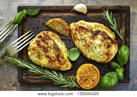 Grilled spicy chicken breast with herbs on old cutting board.Food background.Top view.