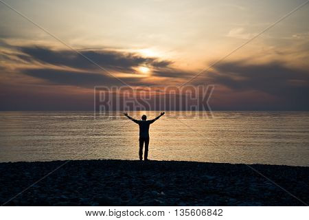 Silhouette of a man with raised arms in the sea water at sunset.