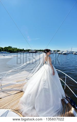 Beauty Bride In Bridal Gown With Lace Veil On A Yacht. Beautiful Model Girl In A White Wedding Dress