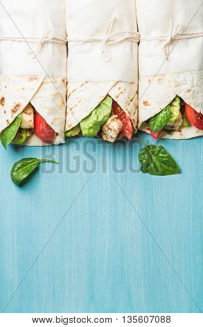 Healthy lunch snack. Tortilla wraps with grilled chicken fillet and fresh vegetables on blue painted wooden background. Top view, copy space