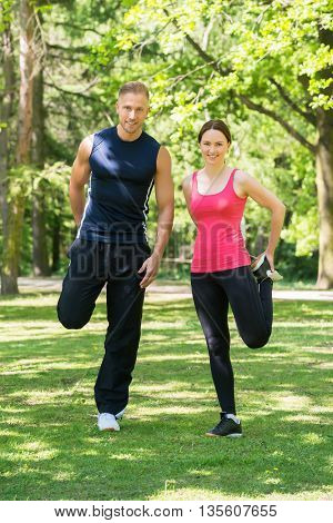 Young Happy Couple Doing Exercise In Park