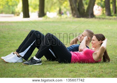 Young Happy Couple Doing Workout Together At Park