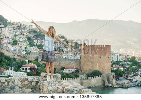 Young blond woman tourist balancing on ancient fortress wall of Alanya castle. Kizil Kule or Red Tower at background. Turkey, Mediterranean region.