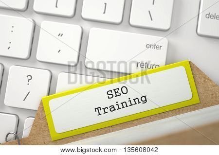SEO Training Concept. Word on Yellow Folder Register of Card Index. Yellow Card File on Background of Modern Metallic Keyboard. Close Up View. Selective Focus. 3D Rendering.