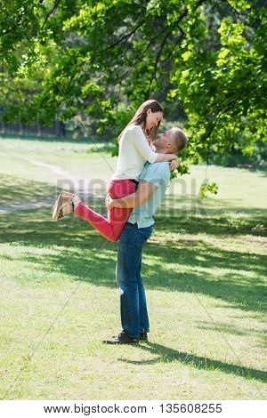 Side View Of Man Lifting Woman At Park