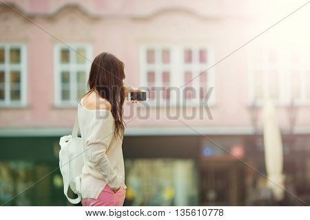 Young caucasian woman sending message and taking self portrait in outdoor cafe at european city