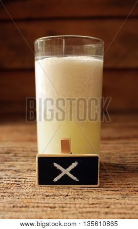 spoiled milk in glass and small wooden concept healthy beacareful unable drink