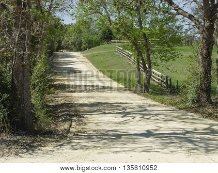 A lonely country dirt road with a wooden fence.