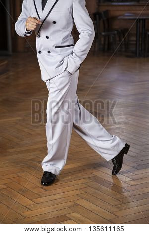 Low Section Of Tango Dancer Performing Cross Step In Restaurant