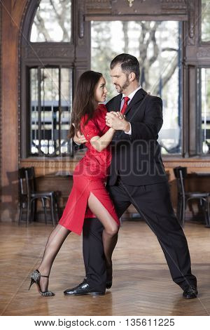 Tango Dancers Performing Leg Wrap Step While Performing In Resta