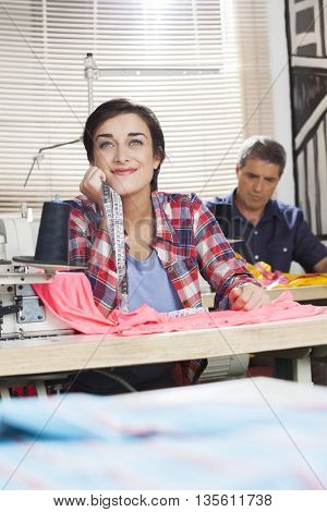 Thoughtful Tailor Smiling While Leaning On Workbench