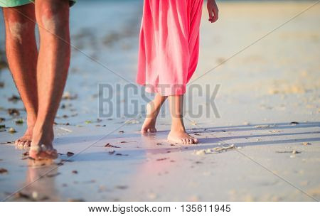 little girl with feet at the white sandy beach